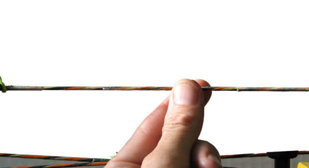 fingers waxing a bow string