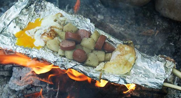 clank - eggs, sausage, potato in a foil made basket cooking on fire