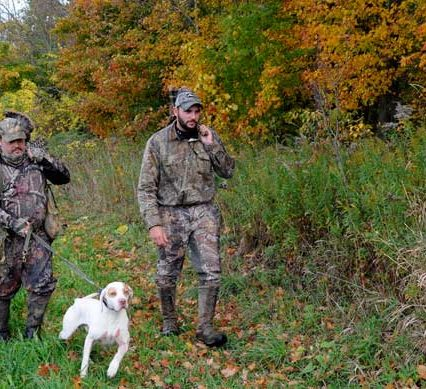 Two guys hunting with a dog