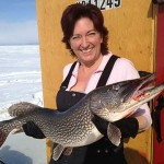 a woman holding a large pike