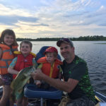 Violet, 5, Emmet, 3, Oliver, 2, and dad Gord Buxton pose with a largie on the Bay of Quinte.