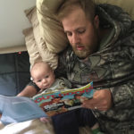 Some people read children's books to their kids. Jackson Beau, 7 weeks, prefers fishing articles.
