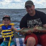 Nate Sharp, 4, with some help from his dad, holds his first fish that he caught on the Ottawa River.
