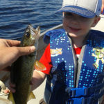 Owen, 2, holds a walleye that his mom caught while out on a family fishing trip.