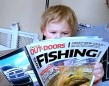 """It's never too early to start. Iain Horne of Manitouwadge submitted this photo of two-year-old McKinnon who likes reading OOD as much as his dad, and pointing out all the """"fishies""""."""