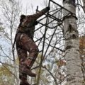 tree stand accidents - a person climbing a tree stand